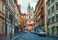 Deserted street with old house and view on tower from cathedral in prague Royalty Free Stock Photo