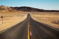 Desertic road to nowhere in death valley surrounded by the desert Stock Photo