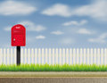 Design of abstract english uk letter box mailbox red at roadside with white fencing on background with white clouds and green Royalty Free Stock Photography