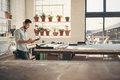 Design business owner checking stock on a clipboard young male standing in his studio workshop figures and his sunny afternoon Royalty Free Stock Photography