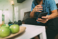 designer man hand using mobile payments online shopping,omni channel,drinking water,sitting on sofa in living room,green apples i Royalty Free Stock Photo