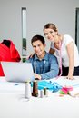 Designers working in workshop portrait of young clothing on laptop together Stock Images