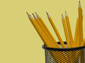 Desk organizer filled with pencils against yellow background Stock Photo