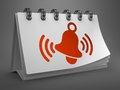 Desktop calendar with red ringing bell icon white on gray background Royalty Free Stock Photography