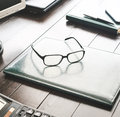 Desktop with leather folder, glasses, calculator and notepad wit Royalty Free Stock Photo