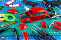 Desktop view assembly and painting of a red retro scale model car vehicle concept background. modeling tools airbrush gun paint Royalty Free Stock Photo