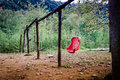 Desolated swings on natural park empty and made by woods and ropes with just one plastic red seat a area this is a Stock Image