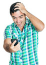 Desperate angry man looking at his mobile phone with a furious expression isolated on white Royalty Free Stock Image