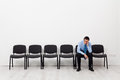 Desperate businessman or employee sitting alone prompting his head Royalty Free Stock Photos