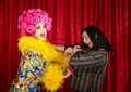 Desperate drag queen with man excited in boa pulling on a Royalty Free Stock Photos