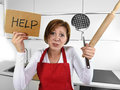 Desperate inexperienced home cook woman crying in stress desperate holding rolling pin and help sign young feeling at domestic Stock Photography