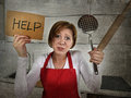 Desperate inexperienced home cook woman crying in stress desperate holding rolling pin and help sign young feeling at domestic Royalty Free Stock Photography