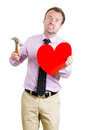 Desperate sad and looking crazy holding a hammer and a heart in his hands portrait of young man isolated on white background Stock Photo