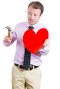 Desperate sad and looking crazy holding a hammer and a heart in his hands portrait of young man isolated on white background Stock Photography