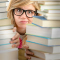 Desperate student teenager look from behind books looking stack of library Royalty Free Stock Photography