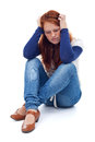 Desperate young girl thinking sitting on the floor isolated Stock Photos