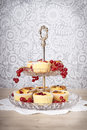 Dessert cakes and cherries on stand side view of red berries silver with vintage style wallpaper in background Stock Photos