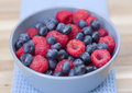 Dessert fresh berries close up in the bowl raspberries and blue on a wooden table Stock Photo