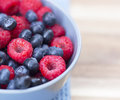 Dessert fresh berries close up in the bowl raspberries and blue on a wooden table Royalty Free Stock Photography