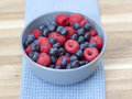 Dessert fresh berries close up in the bowl raspberries and blue on a wooden table Stock Image