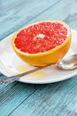 Dessert from grapefruit with honey on a white plate Royalty Free Stock Images