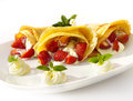 A dessert plate with crepes strawberry fruits whipped cream and mint homemade pancakes Royalty Free Stock Images