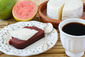 Dessert romeo and juliet goiabada minas cheese coffee brazilian on white plate with cup of fresh goiaba on wooden table Stock Image