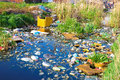 Destroyed nature river that is polluted with various garbage and trash photography Stock Image