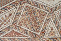 Detail of an ancient colorful mosaic fragment floor small tiles unusual geometric ornament floral and regular forms israel Royalty Free Stock Images