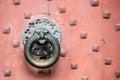 Detail of antique bronze door knocker on old red door Royalty Free Stock Photo