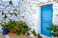 Detail of blue door, white stone wall and colorful flowers