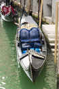 Detail of a blue gondola seat moored in the venice channels Royalty Free Stock Photos