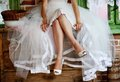 Detail of bridal legs with shoes sitting on the wooden table Royalty Free Stock Photography