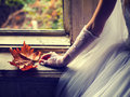 Detail of the brides hand holding autumn leaf while sitting in f front window Stock Photography