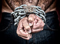 Detail of the chained hands of a man dramatic an adult with strong chain and padlock Royalty Free Stock Photo