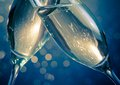 Detail of champagne flutes with golden bubbles on blue light bokeh background Royalty Free Stock Photo