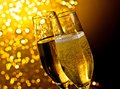 Detail of champagne flutes with golden bubbles on dark golden light bokeh background space for text Stock Photography