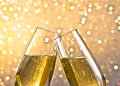 Detail of a champagne flutes with golden bubbles on light bokeh background make cheers space for text Stock Photos