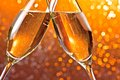Detail of champagne flutes on orange light bokeh background make cheers Stock Photos