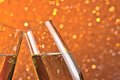 Detail of champagne flutes on orange light bokeh background make cheers with space for text Royalty Free Stock Photo