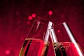 Detail of champagne flutes on red light bokeh background make cheers with space for text Royalty Free Stock Image