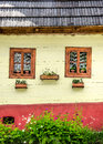 Detail of colorful windows with flowers on old traditional house