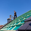 Detail of the construction of a new roof with roofer standing on background Royalty Free Stock Images