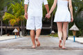 Detail of couple walking on wooden jetty away from camera Royalty Free Stock Photo