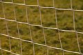 Detail of crossed soccer nets, soccer football in goal net with natural grass on football playground in the background Royalty Free Stock Photo