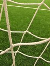 Detail of crossed soccer nets, soccer football in goal net with plastic grass on football playground Royalty Free Stock Photo