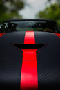 Detail of a dark racing sport car with bonnet scoop vent and red stripes Royalty Free Stock Photo