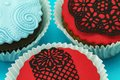 Detail of delicious handmade cupcakes two red colour ones and one blue on blue background Royalty Free Stock Images