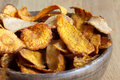 Detail of fried carrot and parsnip chips in rustic wood bowl. Royalty Free Stock Photo