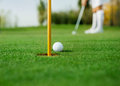 Detail of golf ball and female golfer in background Royalty Free Stock Image